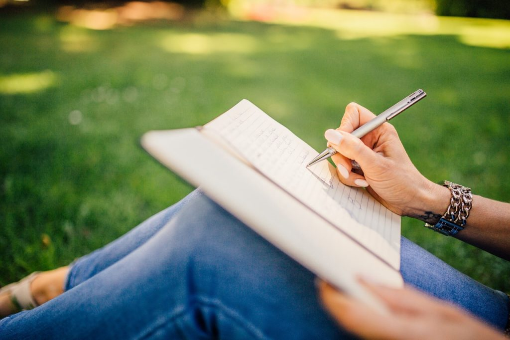women sat on the grass writing in a note book allowing the words to flow