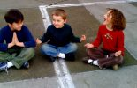 Children sitting in a playground with legs crossed and hands in prayer