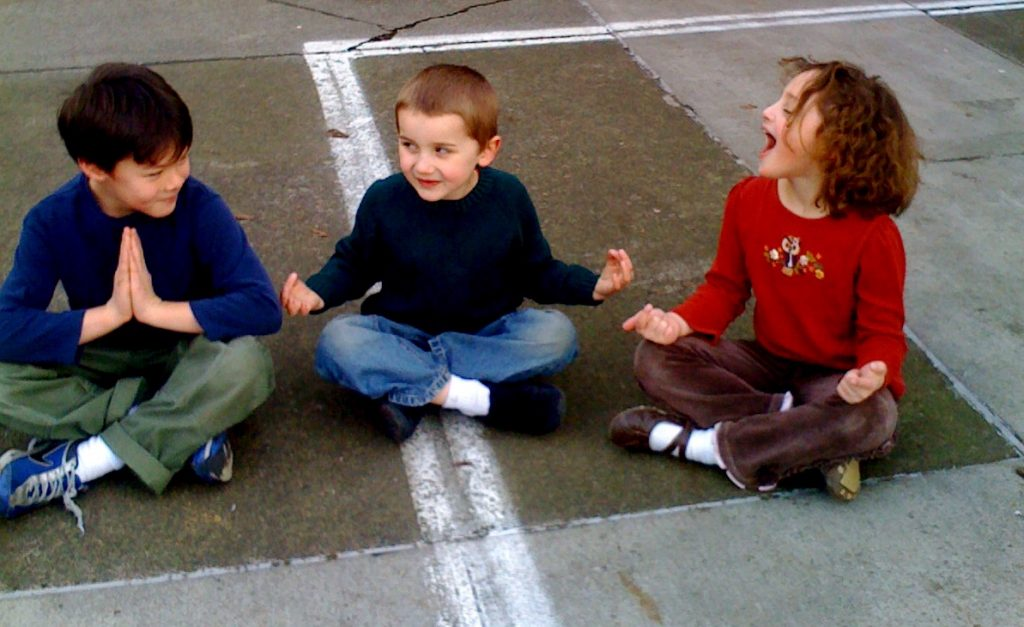 Children sitting in a playground practicing mindfulness