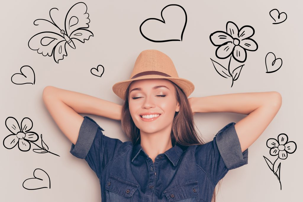 A women wearing a hat, her eyes are closed she is smiling she is at rest